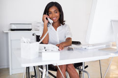 Smiling businesswoman in wheelchair working at her desk Royalty Free Stock Photos