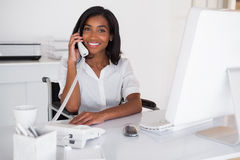 Smiling businesswoman in wheelchair working at her desk Stock Photography