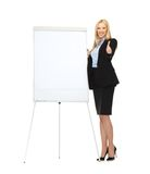Smiling businesswoman with white blank flipchart Royalty Free Stock Photo