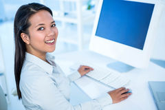 Smiling businesswoman working on computer Stock Photo