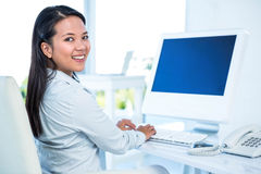 Smiling businesswoman working on computer Stock Photos
