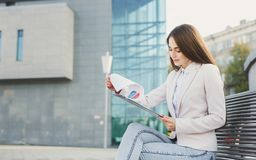 Caucasian businesswoman working with papers outdoors Royalty Free Stock Images
