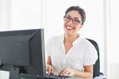 Smiling businesswoman working at her desk Stock Photo