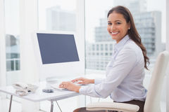 Smiling businesswoman working at her desk Royalty Free Stock Photo