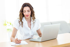 Smiling businesswoman working with her laptop and taking notes Stock Images