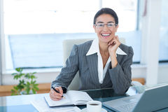 Smiling businesswoman working with her laptop and writing notes Stock Photo