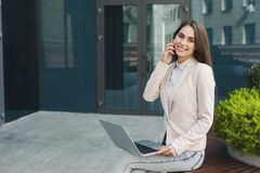 Caucasian businesswoman working with laptop outdoors Stock Photos