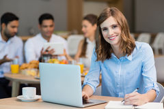 Smiling businesswoman working on laptop while having coffee in office cafeteria Royalty Free Stock Image