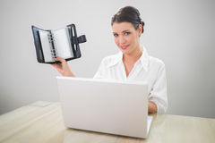 Smiling businesswoman working on laptop holding datebook Stock Photos