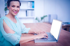 Smiling businesswoman working on laptop Stock Photography
