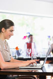 Smiling businesswoman working and laptop and looking on screen Royalty Free Stock Photography