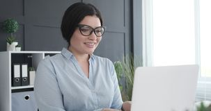 Smiling businesswoman working on laptop. At office stock footage