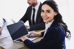 Smiling businesswoman working with laptop in office and looking. At camera royalty free stock image