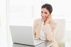 Smiling businesswoman working with a laptop on the phone Royalty Free Stock Photography