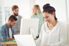 Smiling businesswoman working on laptop Stock Image