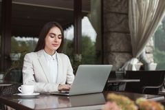 Young businesswoman outdoors working with laptop. Smiling businesswoman working with laptop sitting at summer terrace cafe. Lifestyle portrait of young business Stock Photo