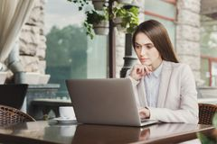 Young businesswoman outdoors working with laptop. Smiling businesswoman working with laptop sitting at summer terrace cafe. Lifestyle portrait of young business Stock Images