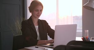 Smiling businesswoman working on laptop. At office desk stock footage