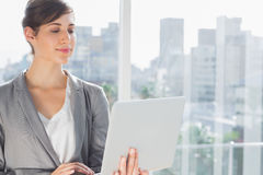 Smiling businesswoman working on laptop Stock Photo