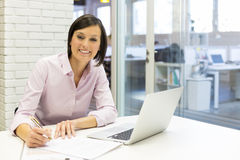 Smiling businesswoman working in office, looking camera Stock Images