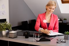 Smiling businesswoman working in office Stock Images