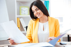 Smiling businesswoman working with papers Stock Photos