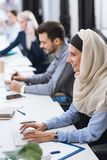 Smiling businesswoman at workplace. Selective focus of smiling arabic businesswoman in hijab typing on keyboard at workplace in office royalty free stock image