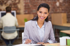 Smiling businesswoman writing diary in office Stock Image