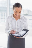 Smiling businesswoman writing on her appointment calendar Royalty Free Stock Photography