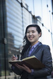 Smiling businesswoman writing in her personal organizer, outside in Beijing Royalty Free Stock Image