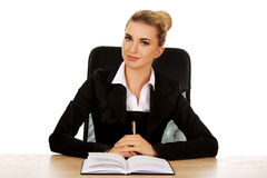 Smiling businesswoman writing note by a desk Royalty Free Stock Images