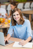 Smiling businesswoman writing on notepad while using laptop in office cafeteria Royalty Free Stock Photo