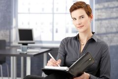 Smiling businesswoman writing notes Royalty Free Stock Photos