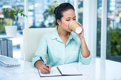 Smiling businesswoman writing notes with a coffee Royalty Free Stock Photo