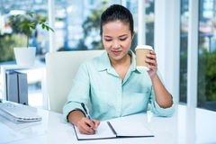 Smiling businesswoman writing notes with a coffee Stock Image