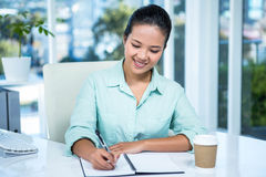 Smiling businesswoman writing notes with a coffee Stock Photography