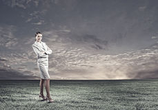 Smiling businesswoman. Young attractive businesswoman standing on green field Royalty Free Stock Photo