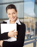 Smiling Businesswomen. Young and happy businesswomen is posing with laptop in front of an officebuilding Royalty Free Stock Photo