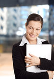 Smiling Businesswomen. Young and happy businesswomen is posing with laptop in front of an officebuilding Royalty Free Stock Image