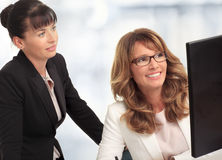 Smiling businesswomen with computer. Businesswomen looking at computer screen together in office, smiling royalty free stock photo