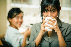 Smiling businesswomen drink coffee in office Royalty Free Stock Photography