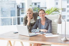Smiling businesswomen looking at camera and working together Royalty Free Stock Photo