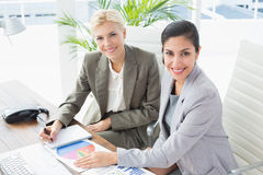 Smiling businesswomen looking at camera and working together Stock Photos