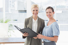 Smiling businesswomen looking at camera and working together Stock Photography