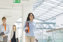 Smiling businesswomen with luggage and file walking at airport Royalty Free Stock Images