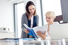 Smiling businesswomen reading book at desk in office Royalty Free Stock Photos