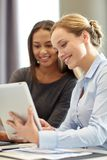 Smiling businesswomen with tablet pc in office Stock Image