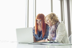 Smiling businesswomen using laptop together in creative office Royalty Free Stock Image
