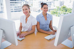Smiling businesswomen working side by side Stock Photo