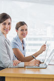 Smiling businesswomen working on their laptops portrait Stock Image
